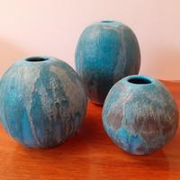 A family of three moon vases, glazed with variegated blues.