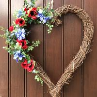 Heart shaped front door wreath featuring red and blue flowers