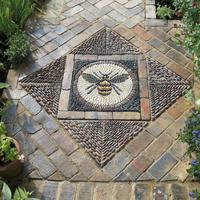 """Bee Pebble Mosaic in """"The Cotswolds'. The design uses stable bricks to compliment colours of the pebble chevrons."""