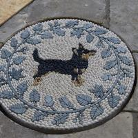 A much loved Lancashire Heeler dog as the central motif of this pebble mosaic. Hand carved Honister slate  leaves and fruits surround the central motif.