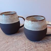 Smooth black stoneware mugs with shiny white glaze, flecked with brown.