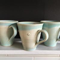 Stoneware; flared mugs; turquoise glaze; plain or spotted version; very practical with comfortable slim handles.  9.5 cm. diameter
