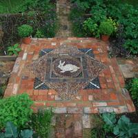 Rabbit pebble mosaic in the vegetable parterre. Local vintage hand made brick surround.