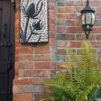 Teasel  pebble mosaic. Intricate teasel head is composed of lots of diamond shaped green Honister slate pieces.