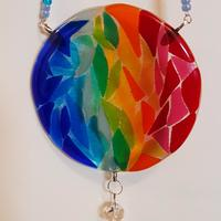 Multicoloured suncatcher and crystal, hanging on a beaded chain.