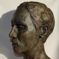Girl's head sculpture in fired clay with painted, gilded and waxed patina.