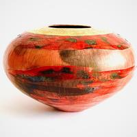 Round sawdust fired vessel with burnished red slip and different tones of red glaze.