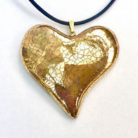Gold lustre heart pendant on an adjustable cotton cord.