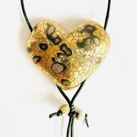 Gold lustre heart pendant with abstract markings and smoke-fired beads.