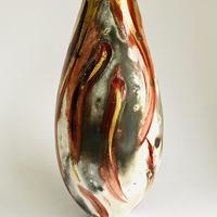 Sawdust fired vessel with different tones of red glaze and gold lustre.