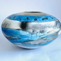 Round smoke-fired pot with expressive blue brush strokes and gold lustre.