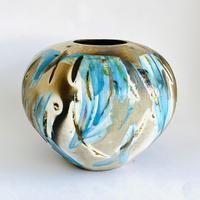 Round sawdust fired vessel with gestural blue glaze brush strokes and gold lustre.