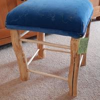 Stool made from field ash , with reused velvet and stitch .