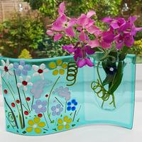 This clever little fused glass vase is perfect for a few sprays of summer flowers.  It is formed onto a wave and is free standing so perfect to pop in a posy.  The aqua blue glass shows a riot of summer flowers.
