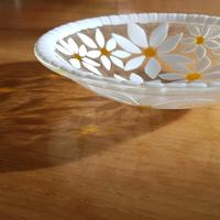 Opaque white daisies with bright yellow centers are set in clear glass.  When the sun shines through this bowl it throws bright yellow reflections on to the surface below.  This fused glass bowl makes a great wedding gift.