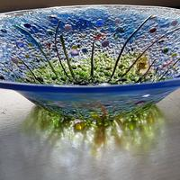This large 28cm diameter fused glass bowl depicts my interpretation of a flower garden.  Transparent greens flow into blues with an impression of summer flowers using reds, yellows, pinks and purples.  This bowl is made to order and can be customised to your colour preferences.