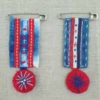 Hand stitched cloth medal brooches
