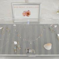 A collection of my jewellery on display at an event, including a multi charm necklace