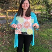Melissa holding a Glass artwork of Citrus fruit