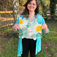 Melissa holding a Glass artwork of Daisies