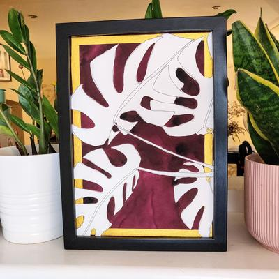 Cheese plant, monstera deliciosa plant, burgundy background, gold art