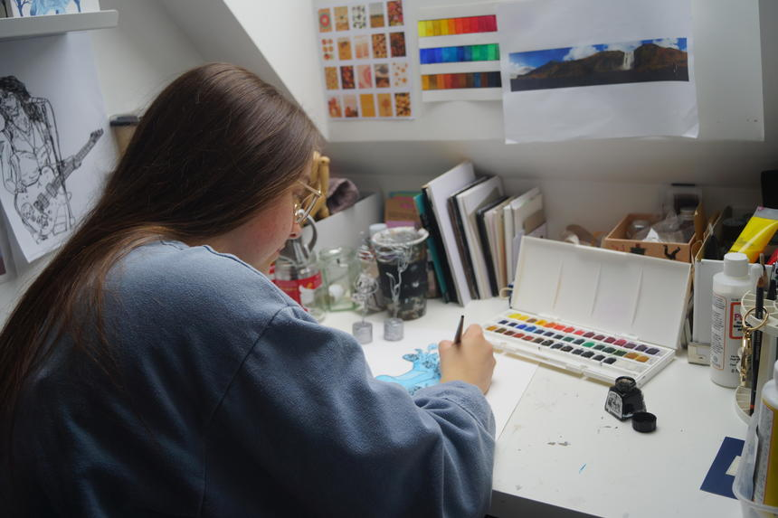 Photograph of Katie working at her desk, doing a blue ink and watercolour illustration of a female figure.
