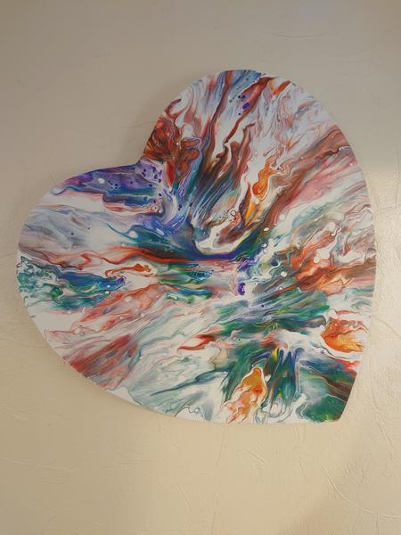 a heart shaped canvas, painted in multicolours.