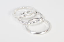 A set of three silver stacking rings, square, round and ball section